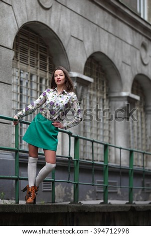 Young woman with turquoise skirt and white stockings standing at a handrail