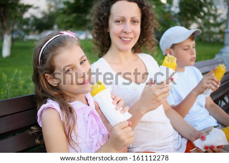 Young woman with two children sitting on a bench and eating boiled corn