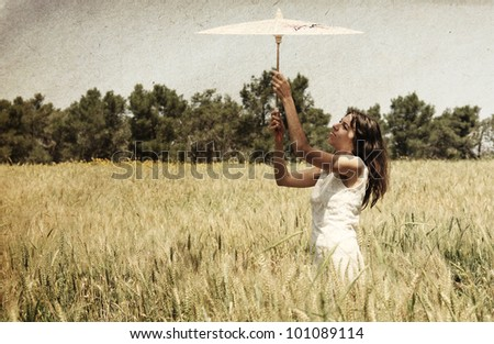 Young woman with umbrella in the field. Photo in old color image style. - stock photo