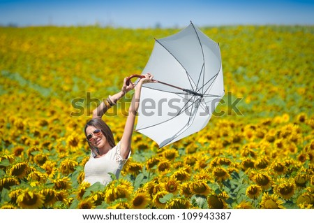 Young woman with umbrella on field in sunflower