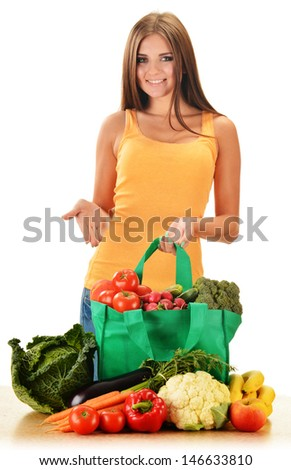 Young woman with variety of grocery products in shopping bag isolated on white