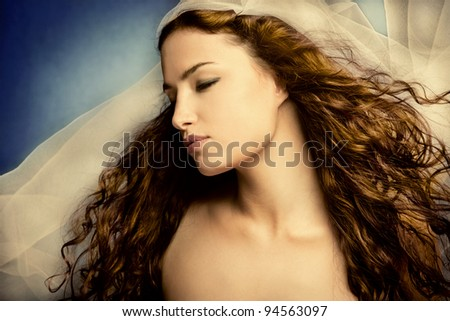 young woman with veil, long curly hair, eyes closed, head in profile, small amount of grain added