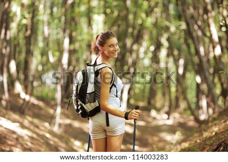 Young woman with walking sticks in a forest
