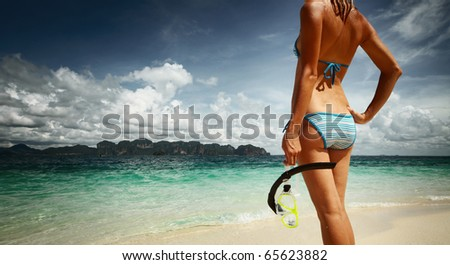 Young woman with wet skin and with a mask standing on sand and going to snorkeling in clear sea - stock photo