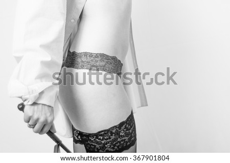 Young woman with whip , shirt and suspenders against white background - stock photo