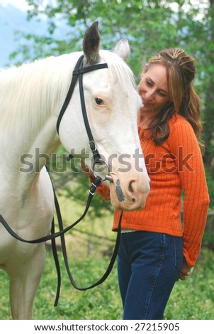Young woman with white horse. - stock photo