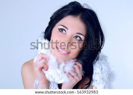 Young woman with white knitted scarf with fur. Enjoy of winter. Happy smile