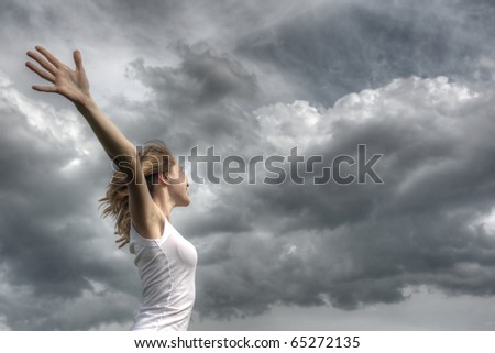 Young woman with white ribbon and raised hands on clouds background - stock photo