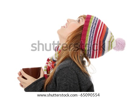 Young woman with winter cap drinking something hot and looking up, isolated on white - stock photo
