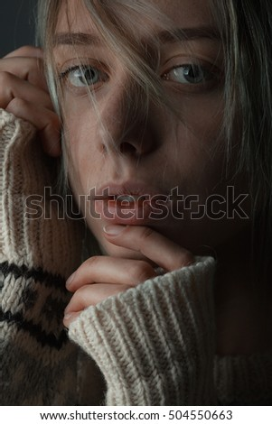 Young woman with wool sweater and hair on face