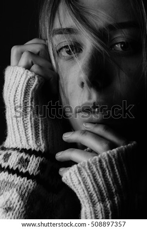 Young woman with wool sweater and hair on face. Black and white