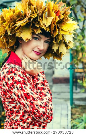 young woman with wreath of autumn maple leaves on the head