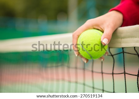 young woman with yellow ball and racket near net - stock photo