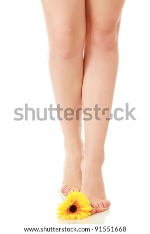 Young woman with yellow gerbera on her toe isolated on white background