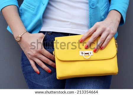 young woman with yellow handbag clutch gray background closeup - stock photo