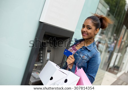 young woman withdrawing cash at the atm - stock photo