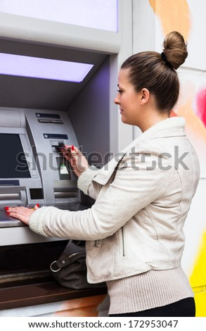 Young woman withdrawing money