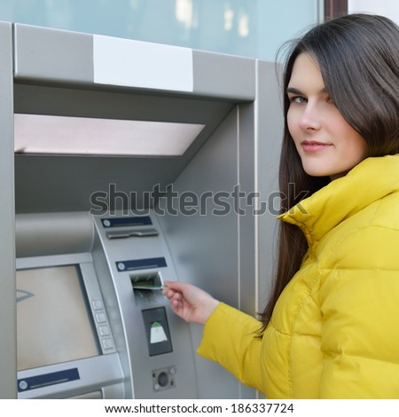 Young woman withdrawing money from credit card at ATM  - stock photo