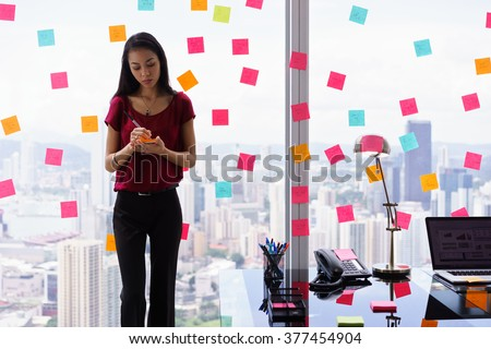 Young woman working as secretary in office, leaning on big skyscraper window. She writes adhesive notes with tasks on window.  - stock photo
