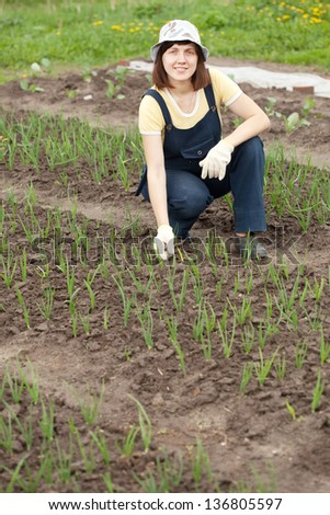 Young  woman  working at  onion plant in spring