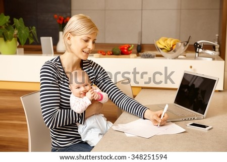 Young woman working from home, holding baby girl on lap. - stock photo