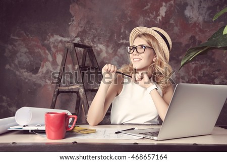 Young woman working in a loft office for laptop. Photo toned style Instagram filters.