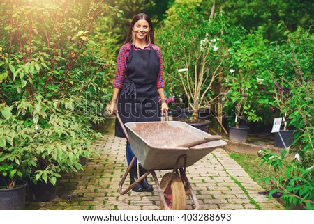 Young woman working in a nursery greenhouse standing on a path amongst potted plants with a wheelbarrow and spade smiling at the camera