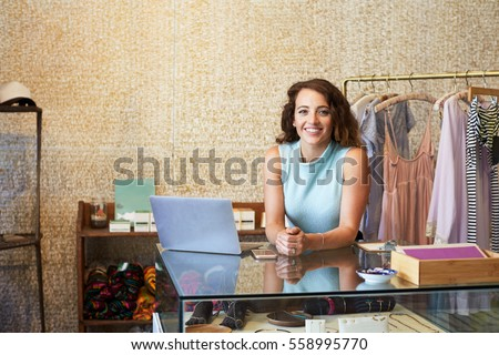 Young woman working in clothes shop leaning on counter