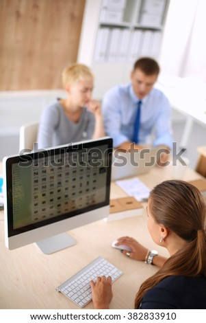 Young woman working in office, sitting at desk - stock photo