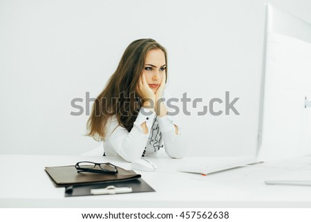 Young woman working in office, sitting at desk, using computer concentrate on read - stock photo