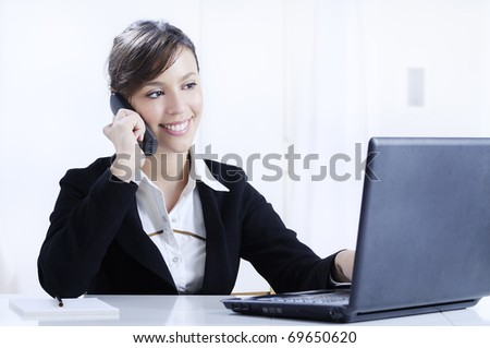 young woman working in office with laptop and smiling