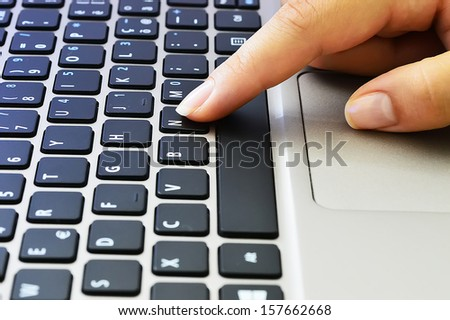 Young woman working on a gray laptop, finger on black keyboard - stock photo
