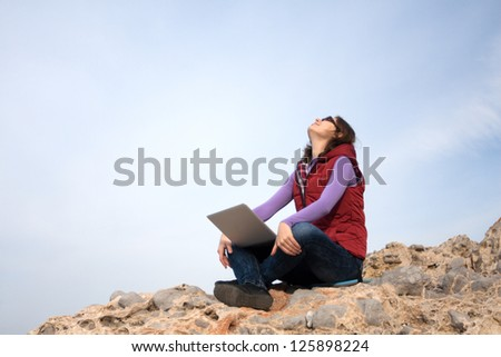 Young woman working on a rock with her laptop - stock photo