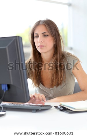 Young woman working on desktop computer