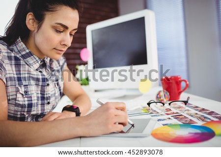 Young woman working on digital tablet on table at creative office - stock photo