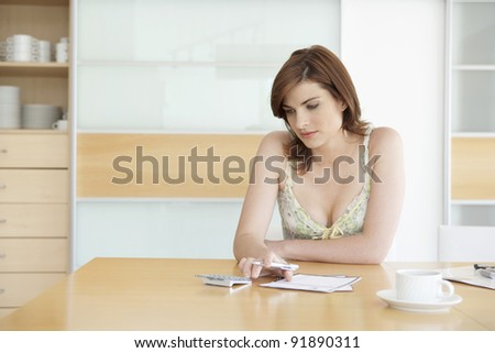 Young woman working on her home finances in her home's kitchen.