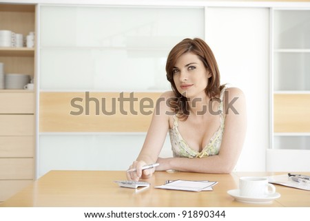 Young woman working on her home finances in her home's kitchen. - stock photo
