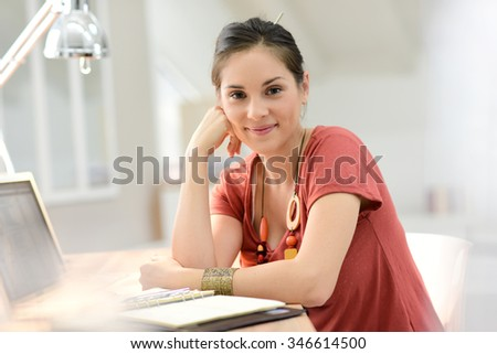 Young woman working on laptop, home-office - stock photo