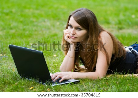 Young woman working on laptop in the field.