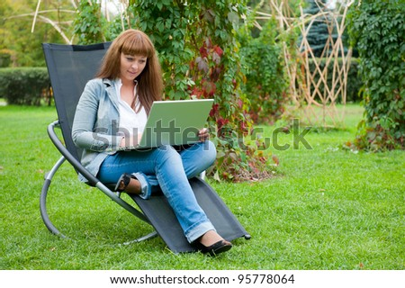 Young woman working on laptop in the park - stock photo
