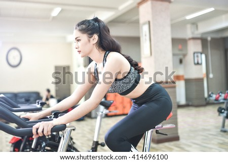 young woman working out at spinning class against fitness gym, waist up - stock photo