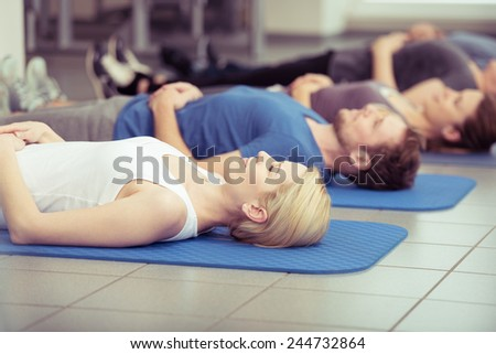 Young woman working out in a gym class doing aerobics breathing exercises lying on a mat, close up upper body in a health and fitness concept - stock photo