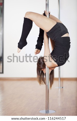 Young woman working out in a pole dancing class