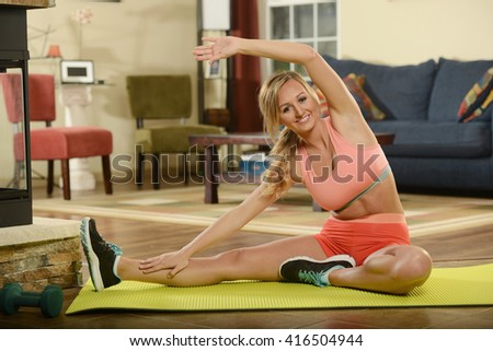 Young woman working out on a mat at home - stock photo