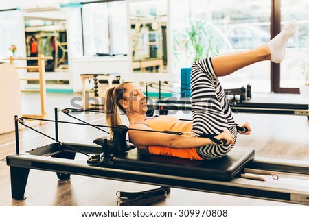 Young woman working out on a pilates reformer - stock photo