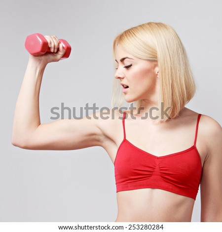 young woman working out with dumbbells on a grey background - stock photo