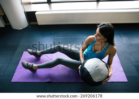 Young woman working out with fit ball on yoga mat at gym - stock photo
