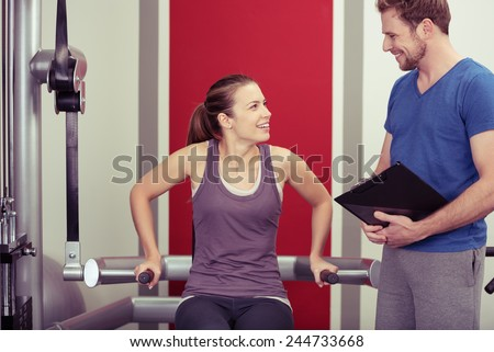 Young woman working out with her personal trainer on equipment in the gym pausing to have a discussion with him concerning her progress