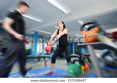 Young woman working out with kettle bell weights, with personal trainer in gym