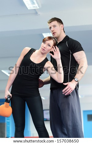 Young woman working out with kettle bell weights, with personal trainer in gym - stock photo